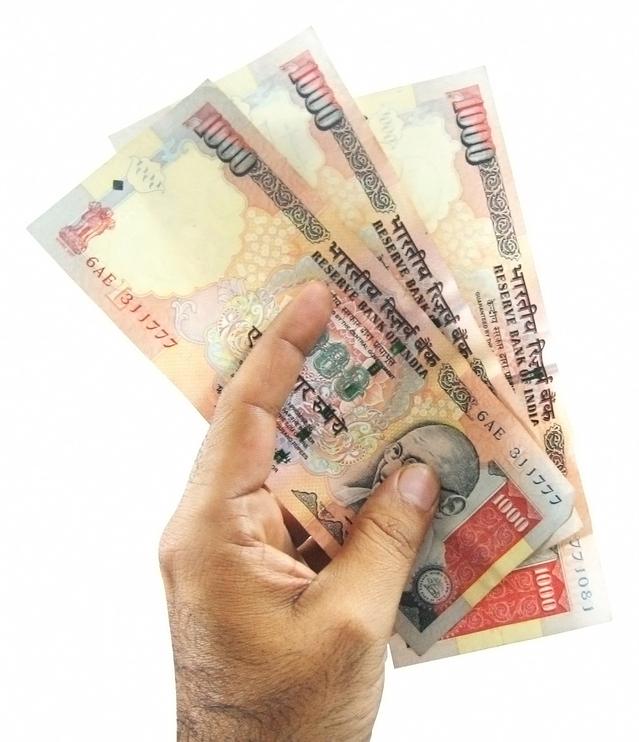 ruka držící tři bankovky
